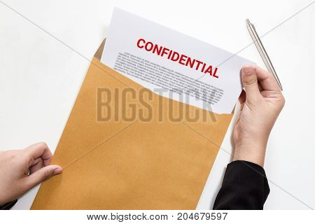 Woman hands holding and looking at confidential document in envelope - business concept