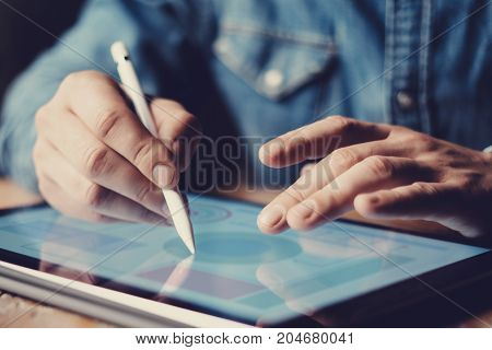 Closeup view businessman using digital pen for pointing device screen.Blurred background. Horizontal.Cropped image