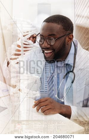 Real astonishment. Close up of excited doctor touching his glasses and expressing interest while working in the cabinet