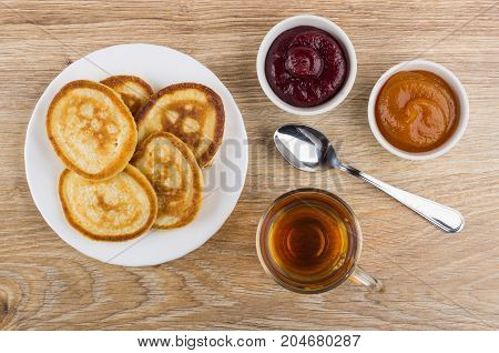 Tea In Cup, Pancakes, Bowls With Jam And Teaspoon