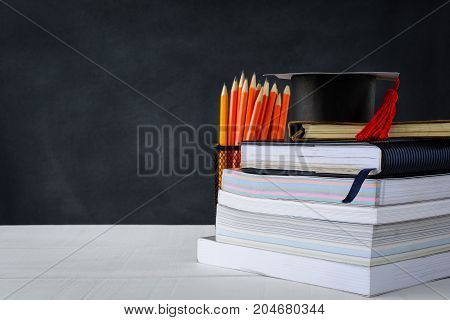 Book And Pencil On White Table Black Board Background