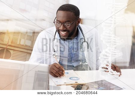 Responsible worker. Close up of optimistic delighted doctor sitting at the table and working with notes while being attentive