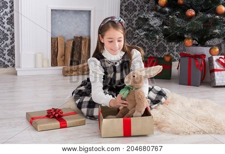 Cute happy girl play with toy rabbit, christmas present on holiday morning in beautiful room. Female child got Xmas gift near decorated fir tree and fireplace. Winter holidays concept
