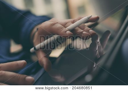 Businessman holding tablet on hand and working at office.Touching fingers tablet screen.Blurred background.Horizontal