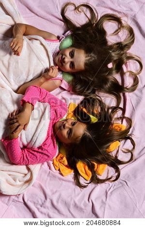 Girls Lie On Pink Bed Sheets Background. Schoolgirls In Pajamas
