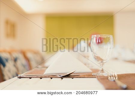 Simple clean white linen elegant table top at fine restaurant dining experience.