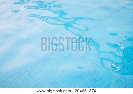 Water ripples on blue tiled swimming pool background. View from above.