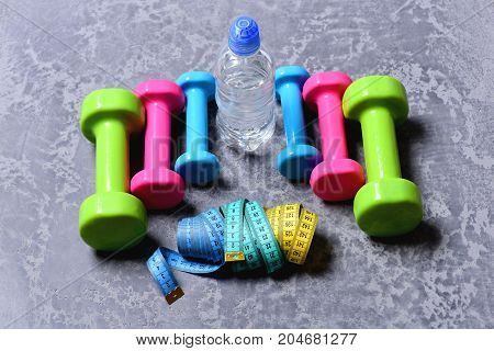 Barbells, Colorful Tape Measures And Water Bottle Placed In Pattern