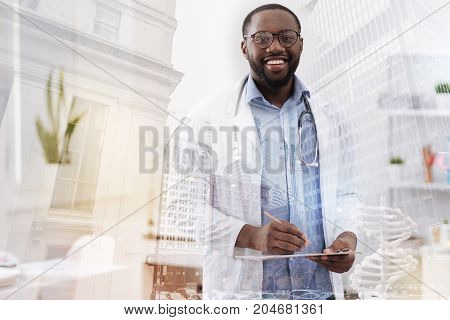 High quality service. Skilled pleasant medical worker holding notes and a pencil in the hand while expressing optimism