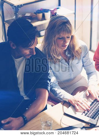 Two young coworkers working on notebook computer at sunny office.Woman holding paper documents and pointing on notebook screen. Vertical.Blurred background