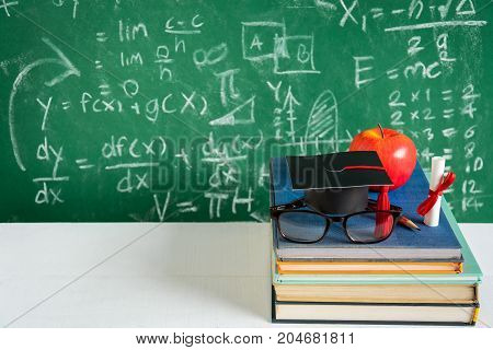 Apple Knowledge Symbol and Pencil Books on the desk with board background.Education concept school