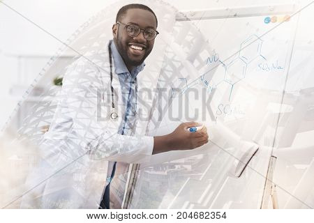 Look here. Waist up of young excited chemist standing at the board while using marker pen and putting down important information