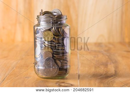 Glass jar full with coin on the table