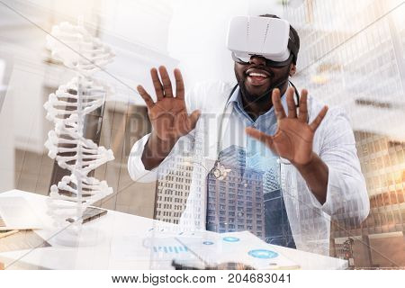 Magic world. Close up of astonished young doctor wearing virtual reality glasses while putting palms forward