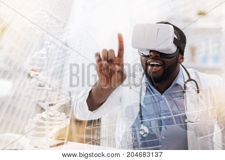 Full of interest. Close up of young excited researcher wearing virtual mask while putting his finger forward and expressing surprise