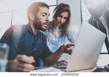 Group of coworkers sitting at the wooden table and working together on new startup project in modern loft office.Horizontal.Blurred background