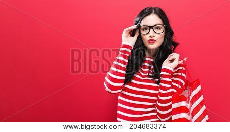 Young woman holding a shopping bag on a red background