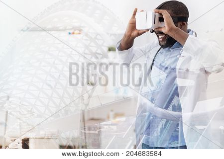 Strongly excited. Waist up of young enthusiastic doctor trying virtual mask while touching it with both hands and expressing happiness