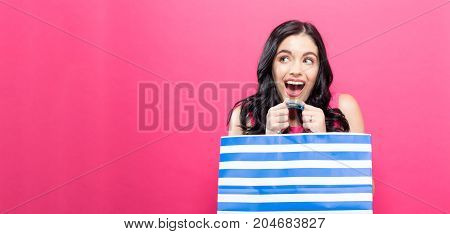 Young woman holding a shopping bag on a pink background