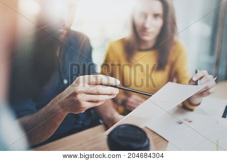 Teamwork process concept.Coworkers working at office.Closeup view of male hand pointing on paper document. Horizontal.Blurred background