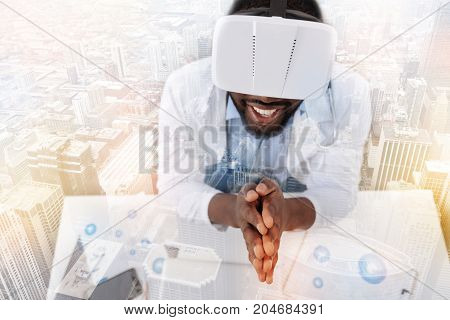 What a fun. Close up of young excited doctor keeping palms together while wearing virtual reality mask