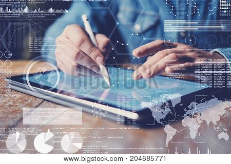 Concept of virtual diagram, graph interfaces, digital display, connections icon.Male hand holding stylus pencil on display of contemporary electronic tablet.Blurred background. Horizontal