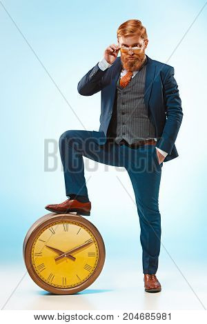 The bearded man in a suit holding retro clock. Isolated on a blue background.