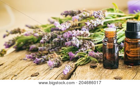 Fresh Lavender And Essential Oil On Wooden Background