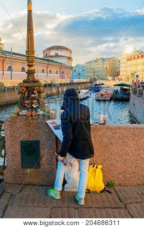ST PETERSBURG RUSSIA-OCTOBER 3 2016. Unidentified artist painting the embankment of Moika river and historic buldings in St Petersburg Russia. City landscape of St Petersburg Russia