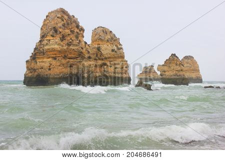 Natural cliff rocks standing isolated in the sea water during starting storm. Foggy unclear background, bad weather conditions, with small waves around beautiful stone cliffs on empty copy space.