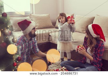 Young family on Christmas morning exchanging presents and enjoying their time together. Focus on the father