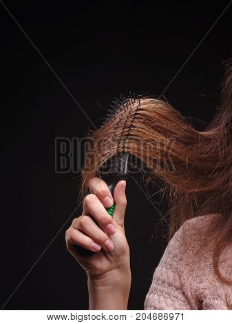 Close-up picture of a female touching her long, brown hair on the black background. Woman's hand pulling hair.