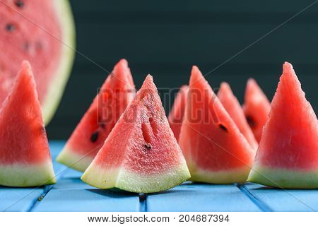 Many bright juicy watermelon slices cut into triangular shape. Summer refreshing snack closeup