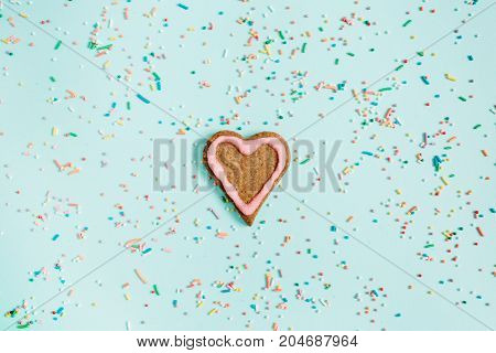 Colorful hand made heart symbol cookie and confetti on blue background. Flat lay top view.