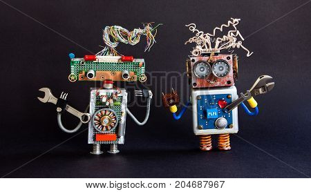 Friendly robots maintenance service concept. Creative design cyborg toys, adjustable spanner hand wrench on black background. Selective focus.