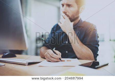 Young handsome man working on mobile computer at sunny office.Coworker making notes on notebook.Horizontal, blurred background