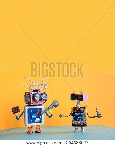Service robots maintenance concept. Creative design cyborg toys with adjustable spanner screwdriver. Yellow background copy space photo