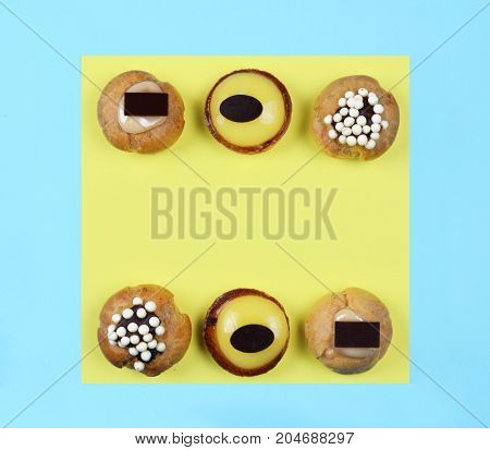 Delicious various pastries on trendy blue and yellow background. Flat lay style.