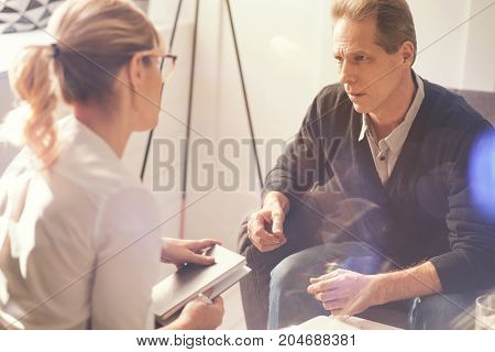 So many problems. Nice gloomy unhappy man looking at his psychologist and speaking to her while telling her about his problems