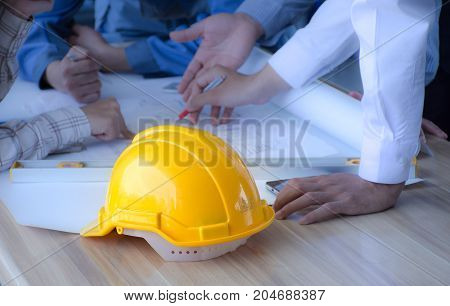 Safety helmet placed on a meeting table engineering team. ,Engineering concept./Selective focus at safety helmet.
