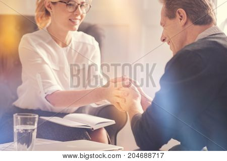 Successful therapy. Joyful happy positive man sitting opposite his therapist and smiling while being in a great mood