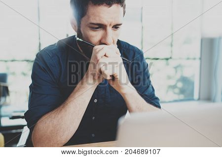 Pensive businessman working at office. Horizontal.Blurred background