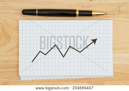 Graph showing upward trend Stack of white graph index cards on wood desk with a pen and graph
