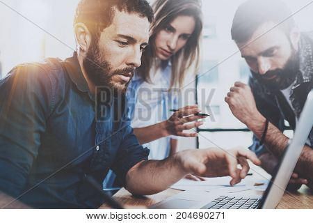 Business team concept.Young professionals discussing new business project in modern office.Group of three people analyze reports on laptop computer.Horizontal, blurred background.Flares