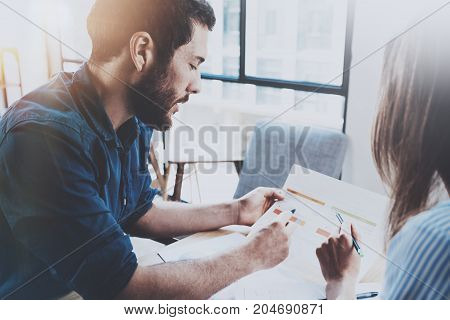 Business partnership process concept.Hispanic young businessman working with business woman at sunny office.Blurred background. Horizontal