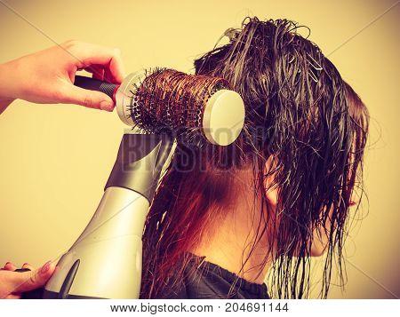 Hairdresser drying dark female hair using professional hairdryer heat modeling