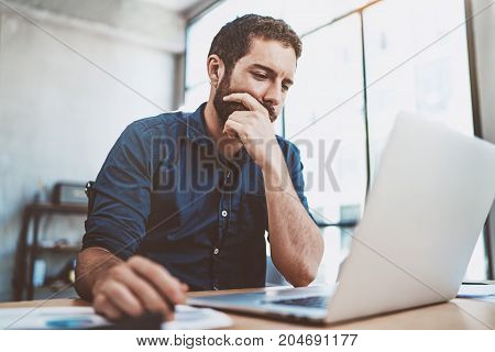 Young businessman working at sunny work place on laptop while sitting at the wooden table.Blurred background.Horizontal