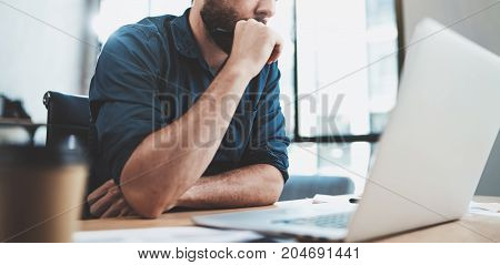 Bearded pensive man working at sunny office on laptop while sitting at wooden table.Businessman reports on notebook computer.Blurred background, horizontal