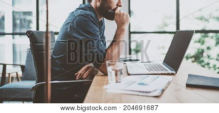 Young pensive coworker working at sunny work place loft while sitting at the wooden table.Man analyze document on laptop display.Blurred background.Horizontal wide
