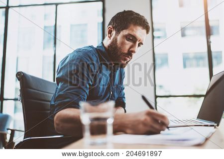 Young attractive man working at sunny loft office on laptop while sitting at wooden table.Businessman analyze digital reports on notebook computer.Blurred background, horizontal